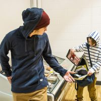 Two brothers stealing bacon in a grocery store.  The older brothers is the lookout while the younger boy steals